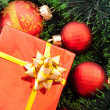 Red Christmas balls and presents among green new year tree — Stock Photo #7288132
