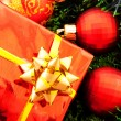 Red Christmas balls and presents among green new year tree - Stock Photo