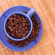 Blue coffee cup and roasted brown coffee beans — Stock Photo