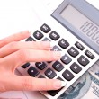 Foto Stock: Calculator and womhand counts money