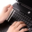 Closeup of men's hands holding credit cart by a  laptop keyboard - Stock Photo