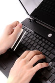 Closeup of men's hands holding credit cart by a laptop keyboard — Stock Photo