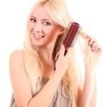 Beautiful young blonde woman brushing her long hair — Stock Photo