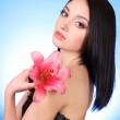 Beautiful young woman with lily flower on blue background — Stock Photo