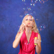Beautiful young woman blowing soap bubbles on blue — Stock Photo