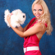 Beautiful blond girl in pink dress with small dog on blue — Stock Photo #7293704
