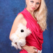 Beautiful blond girl in pink dress with small dog on blue — Stock Photo #7293709