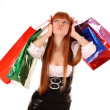 Beautiful, young, redhead woman with color shopping bags in her — Stock Photo