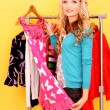 Happy young woman shopping for clothes at the shop — Stockfoto