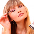 Beautiful young woman applying makeup with brush — Stock Photo