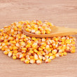 Corn and spoon on brown - Stock Photo