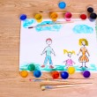 Children's drawings and paint on wooden background - Stock Photo