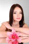 Piękna młoda kobieta z kwiat lilii na szarym tle z m — Zdjęcie stockowe