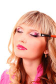 Beautiful young blonde woman with bright make-up and brush on wh — Stock Photo