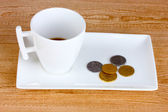 Empty cup of coffee with coins tip on wooden background — Stock Photo