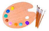Paleta de madera arte con manchas de pintura y un pincel en la parte posterior del blanco — Foto de Stock