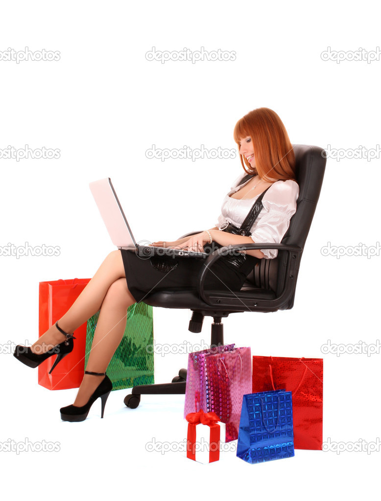 Beautiful, young, redhead woman with color shopping bags shopping over internet. On white background. — Stock Photo #7294110