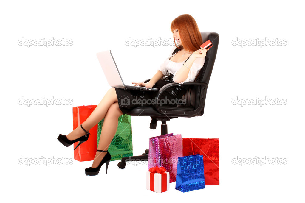 Beautiful, young, redhead woman with color shopping bags shopping over internet. On white background. — Stock Photo #7294115