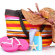 Bright striped beach bag and beach items - Stock Photo