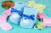 Blue baby booties, socks and pacifier on blue background — Stock Photo