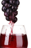 Wine pouring into glass and grapes — Stock Photo