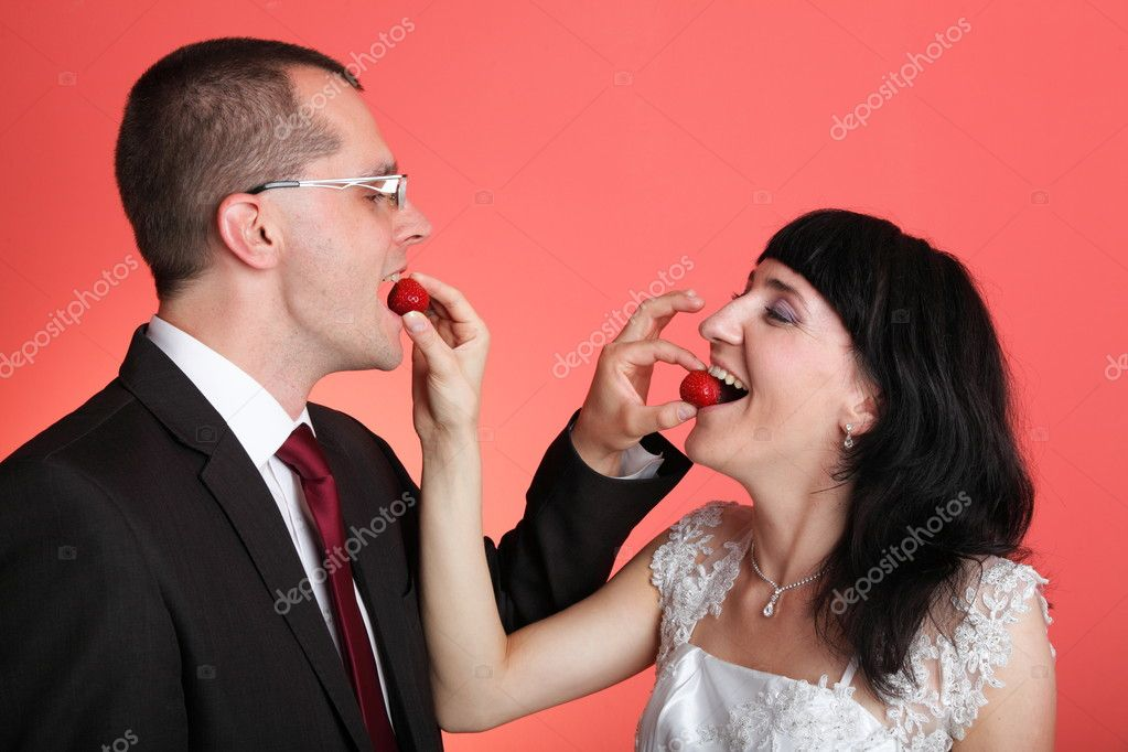 Happy smiling bride and groom young happy couple playfully eating strawbery on red background — Stock Photo #7296534