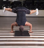 Fitness instructor doing stand on his head — Stock Photo