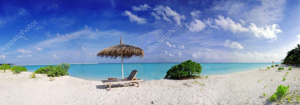 Wide panoramic photo of a beautiful Maldivian beach with parasol and two deck chairs in the front — Stock Photo #6808648
