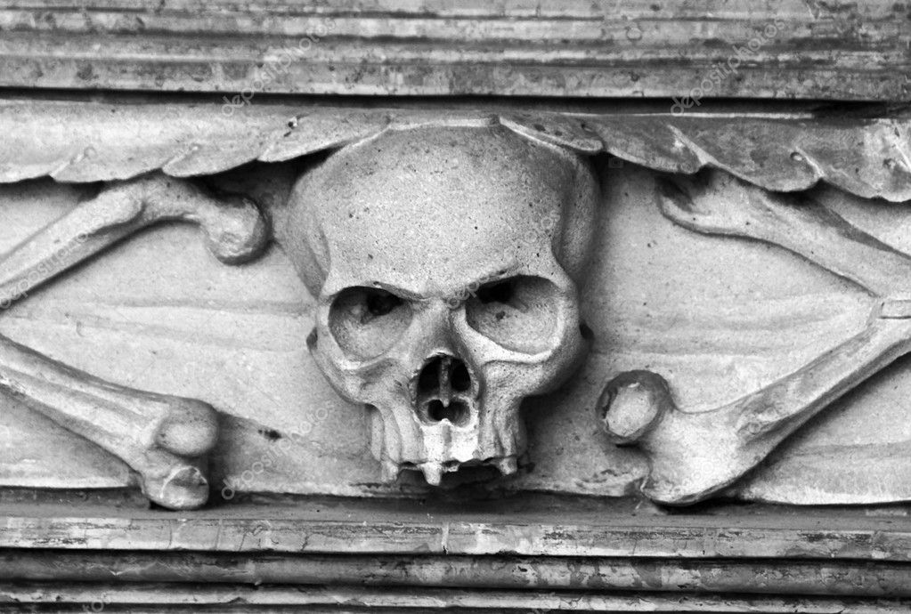 Stone skull carved in tombstone on a grave. Black and white — Stockfoto #6808846