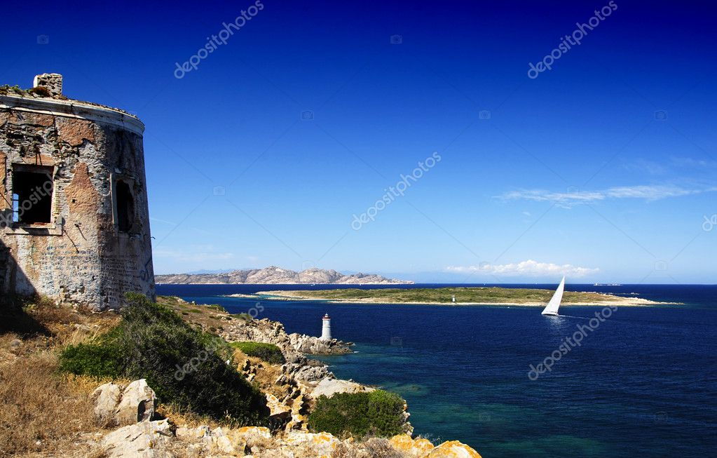 Lighthouse on Sardinian rocks and a yacht sailing in the sea and an old bunker from world war I — Stock Photo #6809162