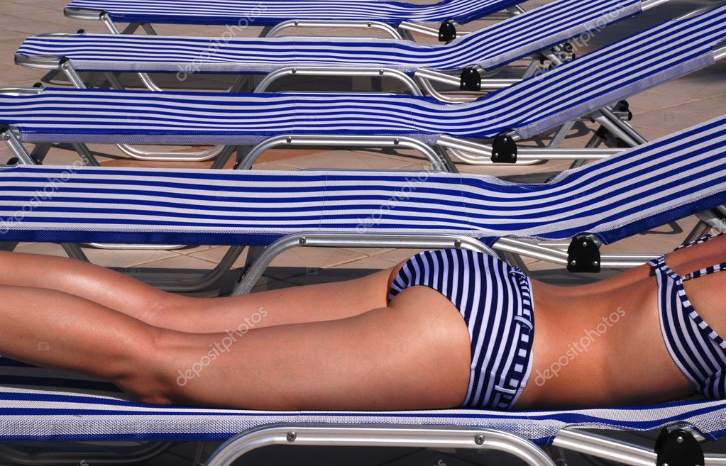 Beautiful girl in a stripped swimsuit laying on a stripped sun bed — Stockfoto #6809851