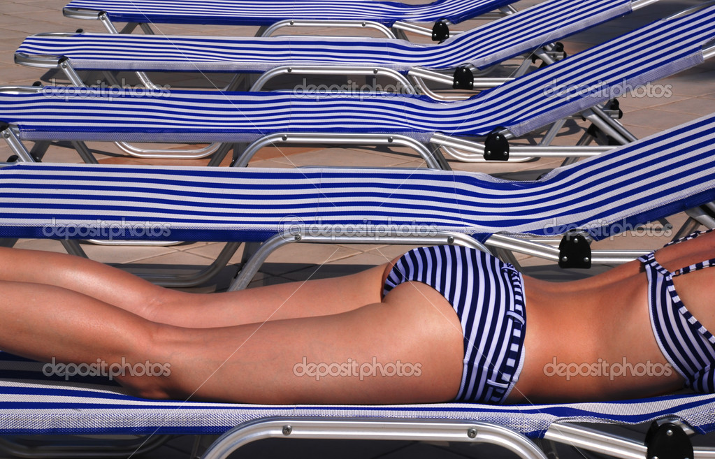 Beautiful girl in a stripped swimsuit laying on a stripped sun bed — Lizenzfreies Foto #6809851
