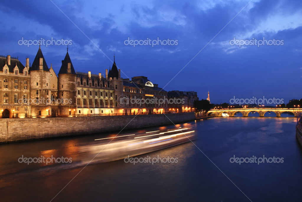 Palais de Justice standing on the banks of river Seine on the island Il de la Cite, Paris - France after the sunset with a boat passing by — Stock Photo #6810684