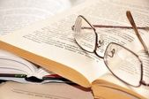 Eyeglasses on open books — Stock Photo