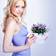 Beautiful blonde with a watering can and a flower — Stock Photo #7027897