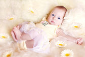 Cute baby lies in the flowers — Stock Photo