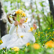 Cute girl in the park with dandelions — Stock Photo
