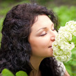 Stock Photo: Cute girl sniffing flowers