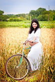 Cute pregnant girl with a bicycle in a field — Stock Photo