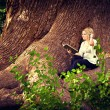 Cute pregnant girl reading on the roots of old trees - ストック写真