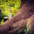 Cute pregnant girl reading on the roots of old trees — Stock Photo