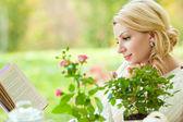 Cute girl in the garden reading a book — Foto de Stock