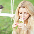 Cute blonde with a bouquet of daisies and swing — Stock Photo