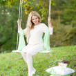 Cute pregnant girl on a swing — Stock Photo