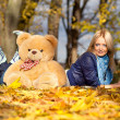 Beautiful girl in the fall leaves with a teddy bear — Stock Photo