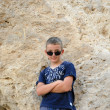 Child boy on the background of the stone cliffs poses — Stock Photo