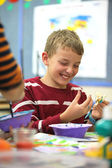 Boy in school artist laughs — Stock Photo