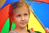 Portrait of little girl with a smile and an umbrella — Photo