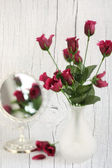 Purple roses in a vase with mirror — Stock Photo