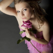 Beautiful lady with a pink rose — Stock Photo